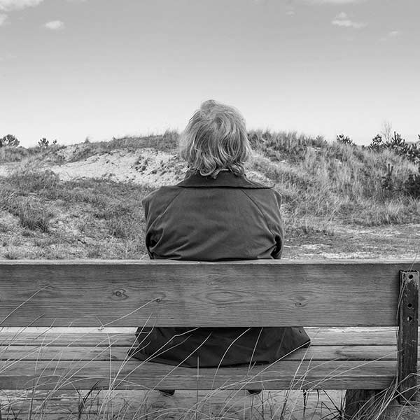 woman sitting on a bench looking out on sand dunes
